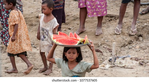 MANDALAY, MYANMAR - NOV 4, 2012 : on the bank of the Irrawaddy River, a little girl sells fresh watermelon to the passengers of the postal boat, near Mandalay on November 4, 2012