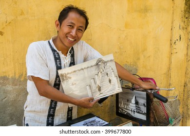 Mandalay, Myanmar - November 18th, 2014: A friendly student offers his paintings to tourists visting his town.