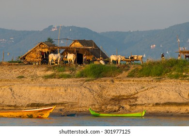 Mandalay, Myanmar - November 19:  Farmers at a bank of Irrawaddy River prepare for their daily work in the early morning sun. November 19, 2015 in Mandalay, Myanmar