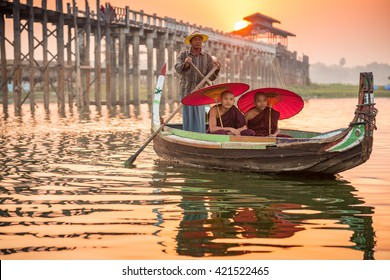 MANDALAY, MYANMAR-4 FEBRUARY 2016: Burmese boatman and buddhist novices  sitting in boat for receiving food offer, morning sunset at U Bein bridge across the Taungthaman Lake, Mandalay, Myanmar