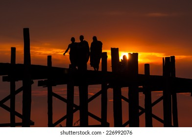 Mandalay,Myanmar-March 16,2011 : Unidentified Myanmar monks walking on U-Bein bridge in sunset in Mandalay, Myanmar. The U-Bein bridge is the longest teak bridge in the world, 1.2km lenght.