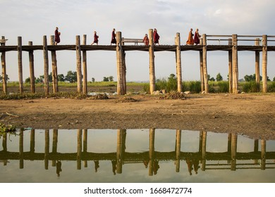 Mandalay/Myanmar-October 6th 2019: A group of Burmese monks are crossing the U Bein Bridge to collect food. U Bein Bridge is the longest teak bridge in the world that is popular with tourists.