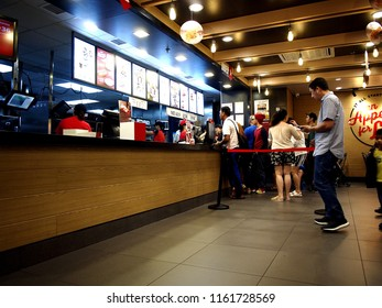 MANDALUYONG CITY, PHILIPPINES - AUGUST 12, 2018: Customers lines up to place their orders at a counter of a fastfood restaurant.