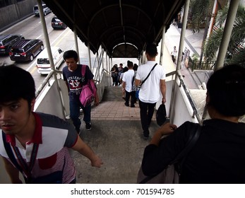 MANDALUYONG CITY, PHILIPPINES - AUGUST 18, 2017: People climbing up and down a staircase of an overpass bridge leading to an MRT station.
