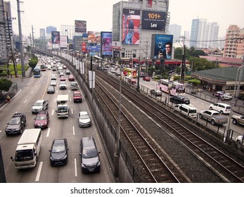 MANDALUYONG CITY, PHILIPPINES - AUGUST 18, 2017: Private and public vehicles passing along EDSA and the Boni MRT Station in Mandaluyong City, Philippines.