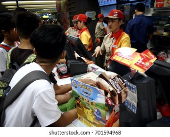 MANDALUYONG CITY, PHILIPPINES - AUGUST 19, 2017: Fastfood chain employees take food orders from queueing customers.