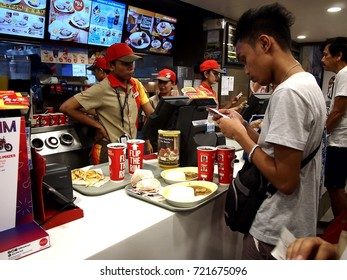 MANDALUYONG CITY, PHILIPPINES - SEPTEMBER 24, 2017: A fastfood chain cashier takes the order of a customer.
