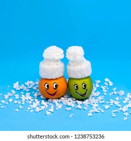 Mandarin and lime in form of funny people in white knitted hats. Creative concept: preservation of fresh fruits in winter. Minimal style