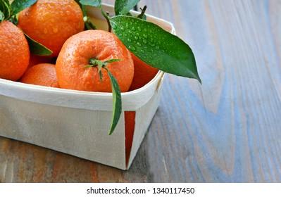 A lot of mandarin orange or mandarine in basket for sale in supermaket with wooden floor