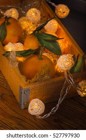 Mandarin orange in the wooden tray with christmas lights.