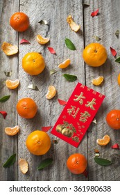 """Mandarin oranges and Chinese new year red packet with text """"Good luck and great fortune"""" printed on rustic wooden background."""