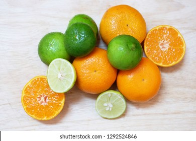 Mandarin oranges and limes on wooden board.