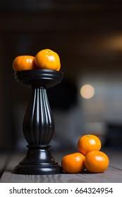 Mandarin oranges on pedestal and rustic wood table.