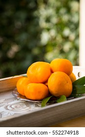 Mandarin oranges on wooden tray and vintage plate