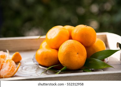 Mandarin oranges in vintage plate on wooden tray