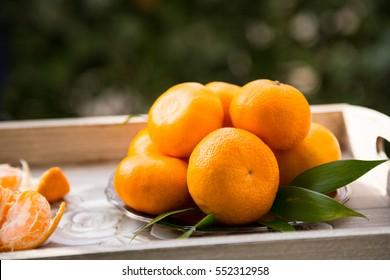 Mandarin oranges in vintage plate on wooden tray