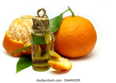 Mandarin, tangerine citrus fruit, with green leaf, isolated on white background. Cosmetic Essence, perfume oil natural plant product in a glass bottle.  Pile of a fresh citrus.