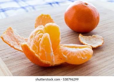 Mandarin, tangerine citrus fruit  slices on on a wooden background.