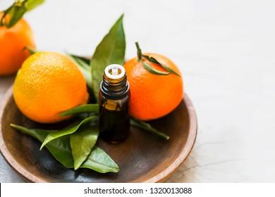 Mandarines essential oil bottle, aromatherapy citrus oil with mandarine fruits