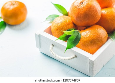 Mandarines and leaves  in a box on light blue background. Selective focus, space for text.