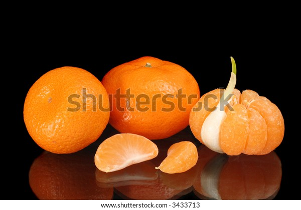 Mandarines, one of them peeled with one segment replaced by garlic clove, and two separate mandarin segments, on black reflecting surface