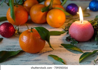 Mandarins in the New Year and Christmas, sweet delicacy and treat for children and adults, decor with candles on Christmas and New Year
