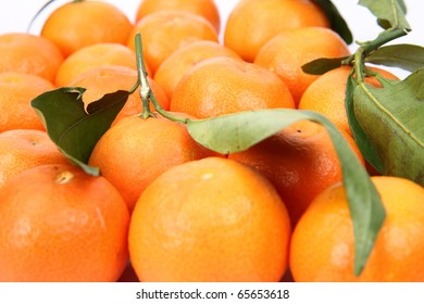 Mandarins, some with leaves, on white background