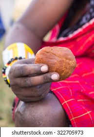 Mandazi, African doughnut held by a Maasai warrior.