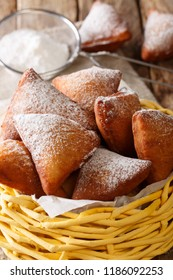 Mandazi, also known as thedaboorSouth Sudanese Coconut Doughnut close-up in a basket on a table. Vertical
