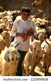 Mandi,Himachal Pradesh,India - April 13 2018: Goatherd herding goats while fixing his sandal. Young asian child goatherd herding and tending goats during vocational activity while fixing his sandals