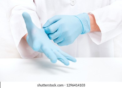 man-doctor wears medical gloves on while standing against a white background.