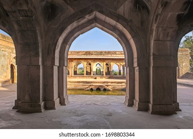 Mandu ,14 February, 2010: View   through  arched pillars  showing royal bathing pool outdoors in background  from Sultan Baz Bahadur Palace, Mandu, Madhya  Pradesh, India,Asia