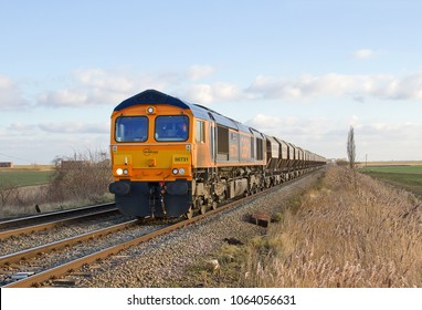 MANEA, CAMBRIDGESHIRE, UK - FEBRUARY 6, 2015: GBRf Class 66 No. 66731 passes through Manea, with a Middleton Towers to Goole Glassworks working, hauling a train of loaded sand hoppers.