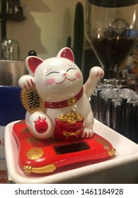 maneki neko on deck coffeshop with coffee background