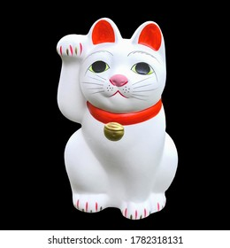 """Maneki-neko (the """"beckoning cat"""") isolated on black background easy to remove. It is a common Japanese figurine which is often believed to bring good luck to the owner."""