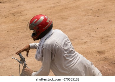 Manga Manor,Lahore,Pakistan,July-2017-02:A Young man (Unknow)  wearing a helmet before riding a motorcycle,