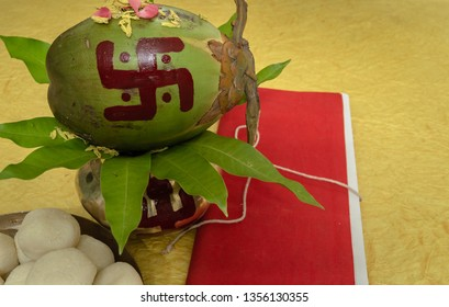 Mangal Kalas With coconut , Flowers And Tree Leafs Along with Rasgulla and Halkhata. With Yellow Background.