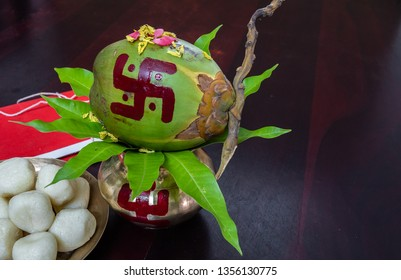 Mangal Kalas With coconut , Flowers And Tree Leafs Along with Rasgulla and Halkhata. with wooden Background.