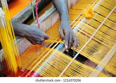 MANGALAGIRI, ANDHRA PRADESH, INDIA, OCTOBER 20, 2018: Overhead view of the hands of a man arranging yellow cotton threads on a mechanical loom to weave a saree.
