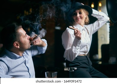 The man-gangster and the beautiful senior woman smoking cigar in a bar
