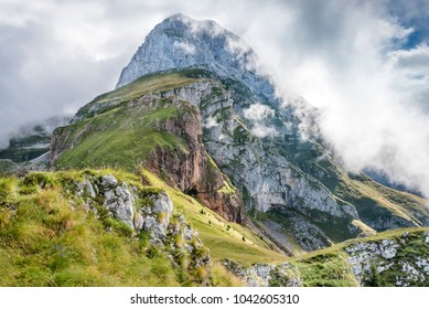 Mangart mountain in clouds, Julian Alps, Slovenia. Morning mists and fog around Mangart rocky mountain peak. Fresh spring green grass in mountain valley.