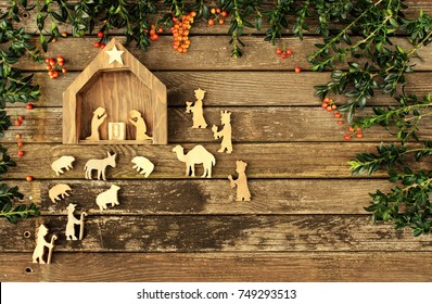 manger scene on rustic wood christmas background with greenery