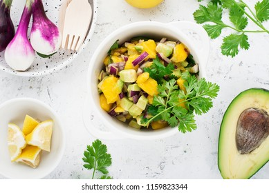 Mango avocado purple onion cilantro celery salsa with ingredients on the table. Top View