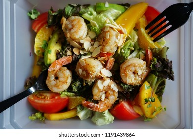 Mango avocado quinoa salad with tomatoes and edamame beans topped with cajun shrimp and sliced almonds in bioplastic take out packaging container on wooden background with black plastic fork and spoon
