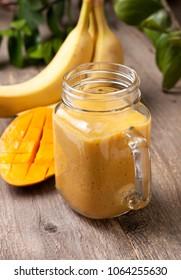 mango banana smoothie in Mason jar on old wooden background