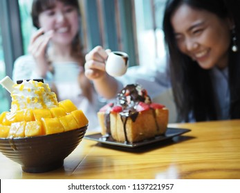 Mango Bingsu (Bingsoo) Korean shaved ice dessert topped with diced mango and cheese in focus with blurred background joyful moment of smiling girls pouring chocolate sauce onto Strawberry Brick Toast.