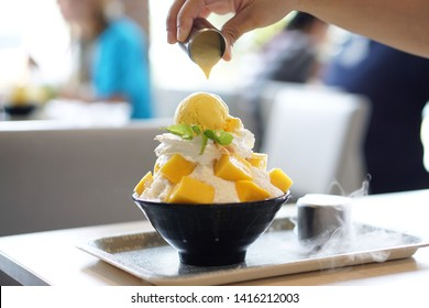 Mango Bingsu (Kakigori) - Korean shaved ice dessert flavor, stuffed with sticky rice, topped with whipped cream and mango ice cream, served with condensed milk, Traditional summer dessert in Korea.