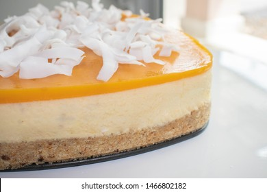 Mango Cheesecake decorated coconut chips on white table.