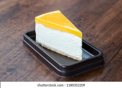Mango Cheesecake isolated in brown tray on the wooden table with copy space.