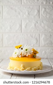 Mango cheesecake with yellow jelly topping, with flowers and fresh mango pieces on white background, vertical composition